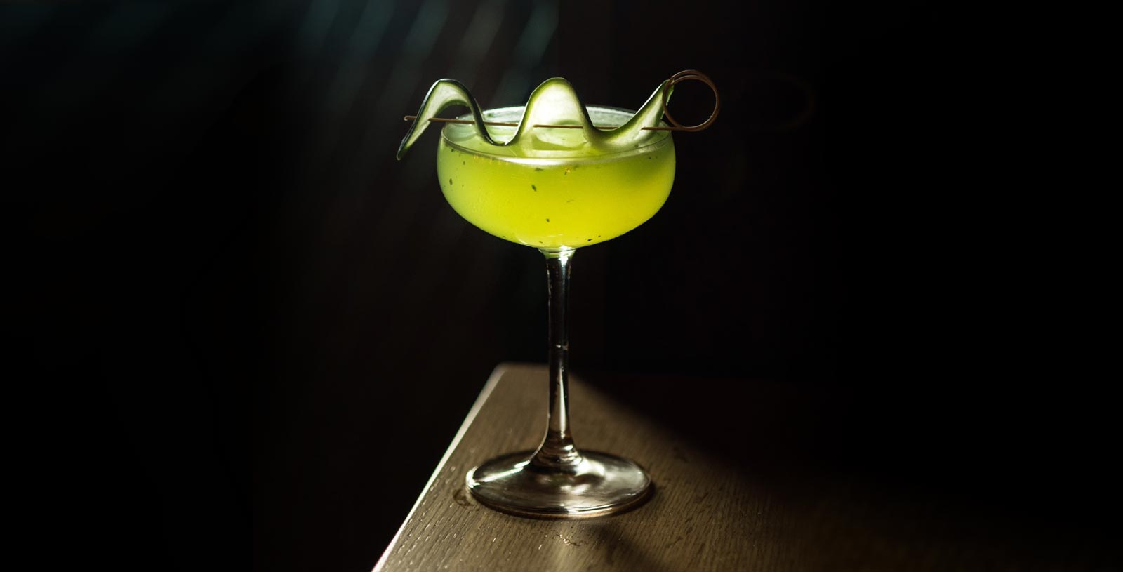 Cocktail called Green Goddess with cucumber garnished